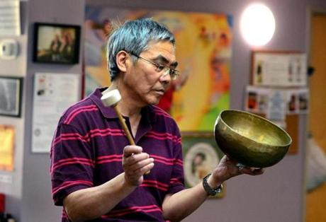 Quincy 07/19/2017: At the Oriental Culture Institute in Quincy , a large group of people gathered for Tom Tam's Healing class. Tom Tam closes the class with the tapping of the metal bowl. Photo by Debee Tlumacki for the Boston Globe (south)