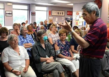 Quincy 07/19/2017: At the Oriental Culture Institute in Quincy , a large group of people gathered for Tom Tam's Healing class. Tom Tam shows the class one of his healing machines. Photo by Debee Tlumacki for the Boston Globe (south)