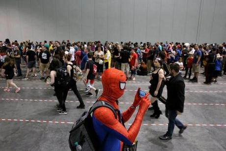 Dressed as Spider-Man, Alejandro Loza, of Manchester, N.H., used his phone to take a video of a line.