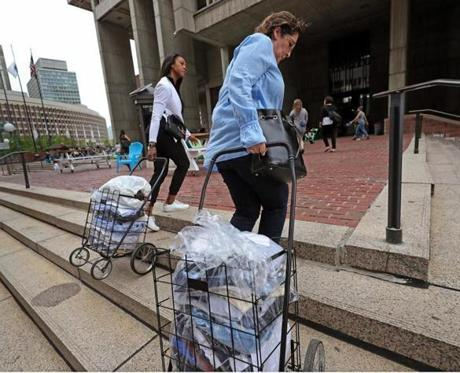 BOSTON, MA - 8/29/2017:L-R Alisha Olsen from Florida and Janet Olsen from Alabama use carts to donate clothing for Texas victims. Janet's father died a month ago so she brought his cothing from his residence in the North End to city hall. Mayor Martin J. Walsh today announced that the City of Boston is sponsoring a 'Help for Houston' Drive starting Tuesday, August 29th through Thursday, August 31st and asks residents to contribute items to those impacted by Hurricane Harvey in Texas - sites: City Hall (3rd Floor Lobby & 5th Floor Mayor's Office Lobby) 1010 Massachusetts Ave (5th Floor) Bolling Building, 2300 Washington St., Roxbury (1st Floor Lobby) 26 Court Street (1st Floor Lobby) Boston Centers for Youth and Families HQ, 1483 Tremont St., Roxbury Boston Centers for Youth and Families sites (David L Ryan/Globe Staff ) SECTION: METRO TOPIC 30helpforhouston