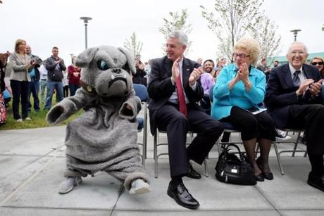 Colin Harer, 12, dressed as the school mascot, a bulldog, receives applause from State Senator John Keenan during a tour of the new building.