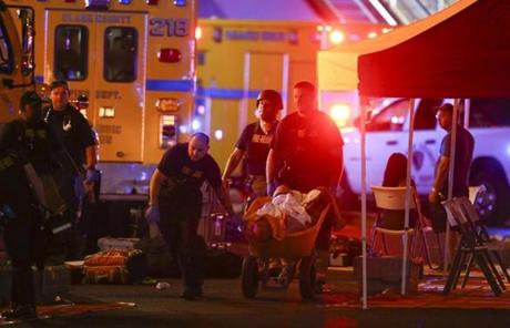 LAS VEGAS SLIDER2 A wounded person is walked in on a wheelbarrow as Las Vegas police respond during an active shooter situation on the Las Vegas Stirp in Las Vegas Sunday, Oct. 1, 2017. Multiple victims were being transported to hospitals after a shooting late Sunday at a music festival on the Las Vegas Strip. (Chase Stevens/Las Vegas Review-Journal via AP)